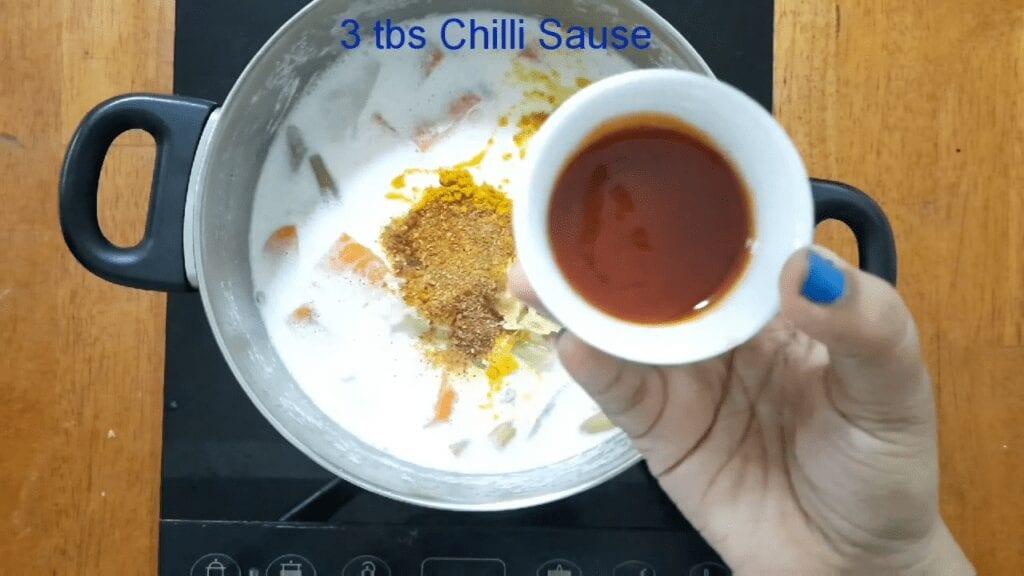 Vegetarian-thai-yellow-curry-add-chili-sauce